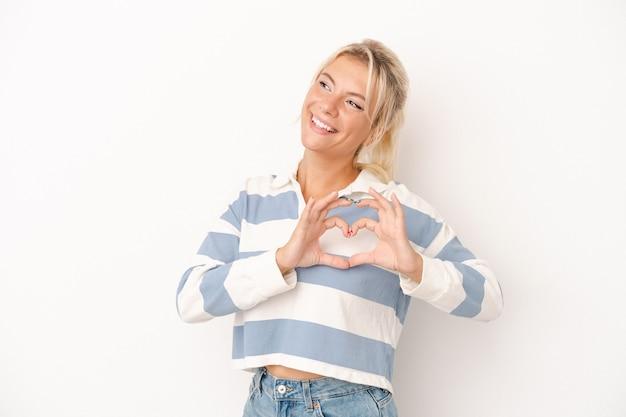Młoda rosjanka na białym tle uśmiechnięta i pokazująca kształt serca rękami.