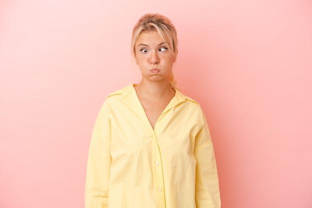Młoda rosjanka na różowym tle dmucha w policzki, ma zmęczony wyraz twarzy. koncepcja wyraz twarzy.