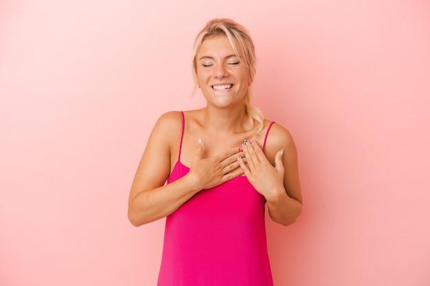 Młoda rosjanka na różowym tle ma przyjazny wyraz twarzy, przyciskając dłoń do piersi. koncepcja miłości.