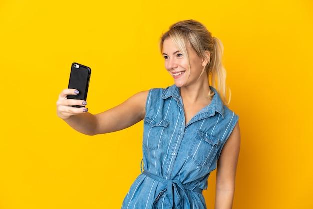 Młoda rosjanka na żółtym tle robi selfie z telefonem komórkowym