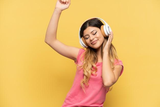 Młoda rosjanka na żółtym tle słucha muzyki i tańczy