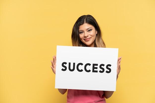 Młoda rosjanka na żółtym tle trzymająca afisz z tekstem sukces ze szczęśliwym wyrazem
