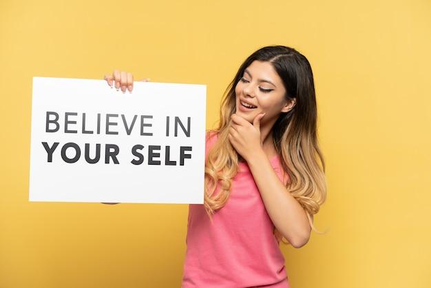 Młoda rosjanka na żółtym tle trzymająca tabliczkę z tekstem uwierz w siebie i myślenie