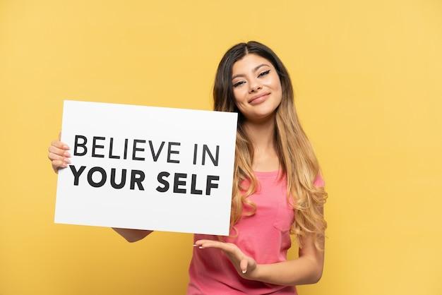 """Młoda rosjanka na żółtym tle trzymająca tabliczkę z tekstem """"uwierz w siebie"""" i wskazującą go"""