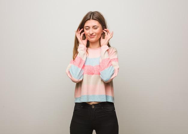 Młoda rosjanka obejmujące uszy rękami