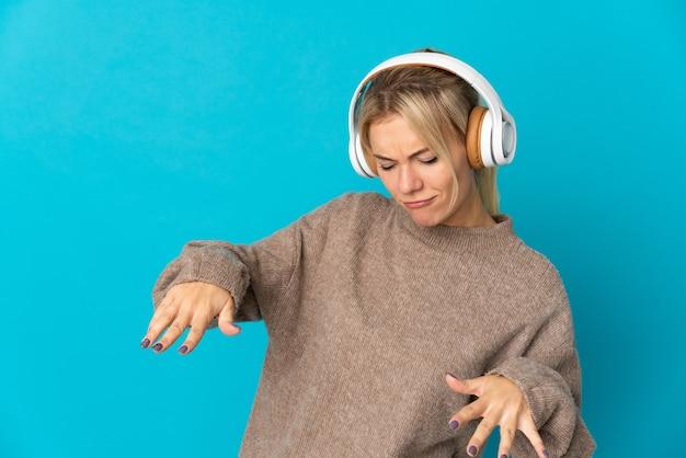 Młoda rosjanka odizolowana na niebieskim tle słucha muzyki i tańczy