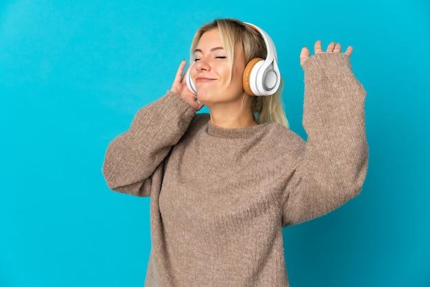Młoda rosjanka odizolowana na niebieskim tle słuchając muzyki i tańcząc