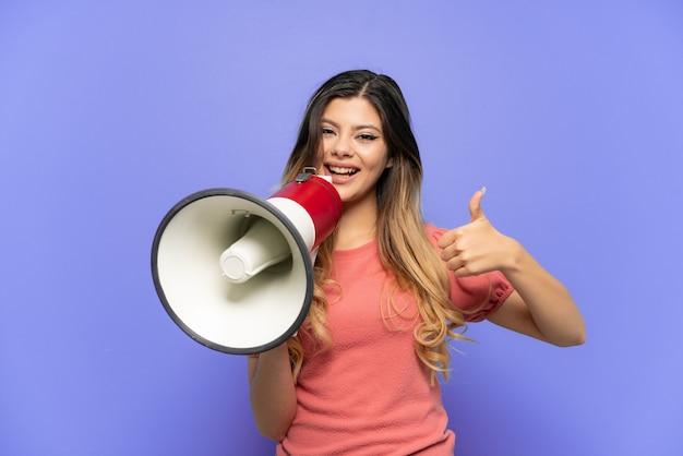 Młoda rosjanka odizolowana na niebieskim tle trzymająca megafon z kciukiem do góry