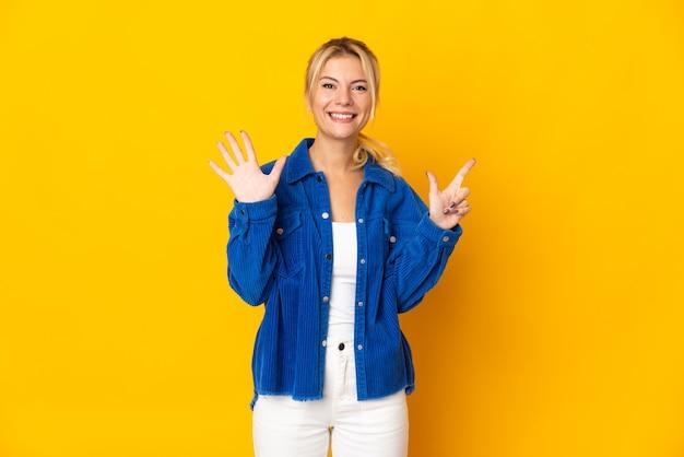 Młoda rosjanka odizolowana na żółtym tle, licząc siedem palcami