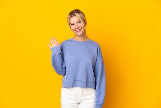Młoda rosjanka odizolowana na żółtym tle salutuje ręką ze szczęśliwym wyrazem twarzy