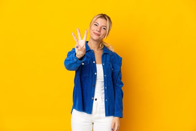 Młoda rosjanka odizolowana na żółtym tle szczęśliwa i licząca trzy palcami