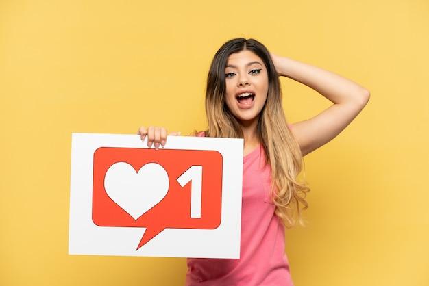 Młoda rosjanka odizolowana na żółtym tle trzymająca afisz z ikoną like ze zdziwionym wyrazem twarzy
