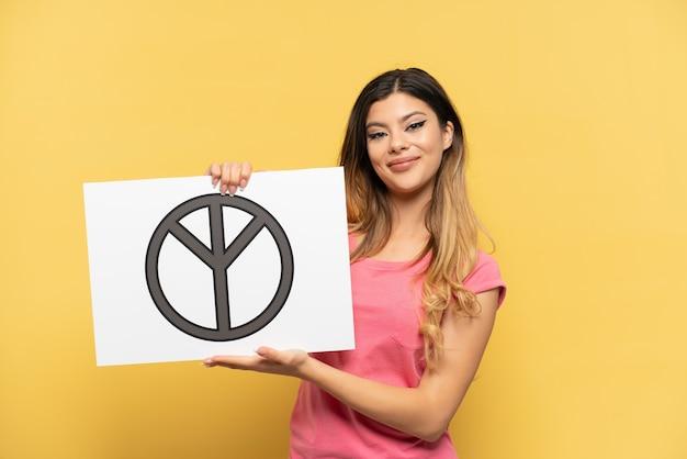 Młoda rosjanka odizolowana na żółtym tle trzymająca afisz z symbolem pokoju ze szczęśliwym wyrazem twarzy