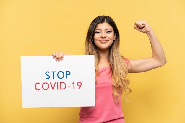 Młoda rosjanka odizolowana na żółtym tle trzymająca afisz z tekstem stop covid 19 i wykonująca silny gest
