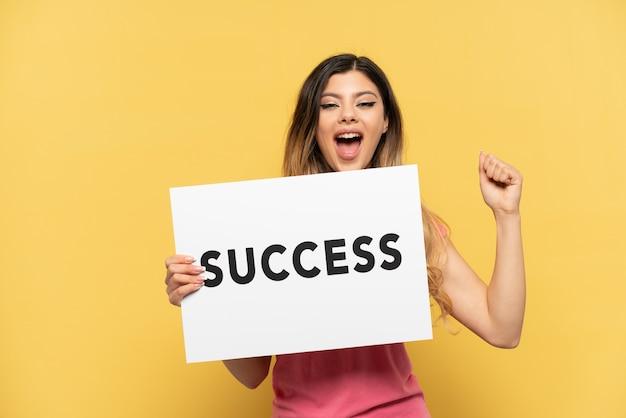 Młoda rosjanka odizolowana na żółtym tle trzymająca afisz z tekstem sukces i świętująca zwycięstwo