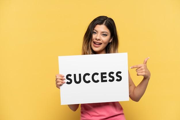 Młoda rosjanka odizolowana na żółtym tle trzymająca afisz z tekstem sukces i wskazująca do przodu