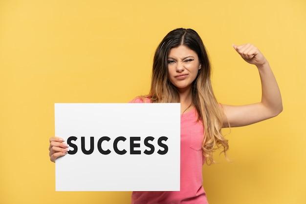 Młoda rosjanka odizolowana na żółtym tle trzymająca afisz z tekstem sukces i wykonująca silny gest