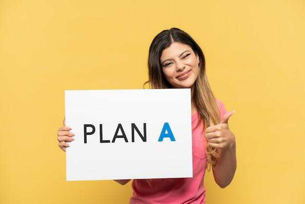 Młoda rosjanka odizolowana na żółtym tle trzymająca tabliczkę z napisem plan a z kciukiem do góry