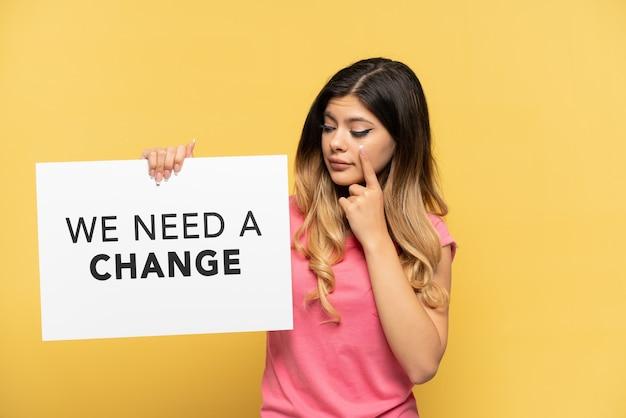 Młoda rosjanka odizolowana na żółtym tle trzymająca tabliczkę z tekstem potrzebujemy zmiany i pokazująca coś