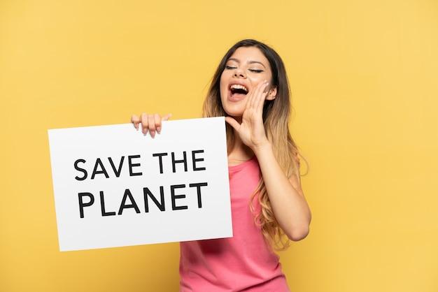 """Młoda rosjanka odizolowana na żółtym tle trzymająca tabliczkę z tekstem """"uratuj planetę i krzycząc"""