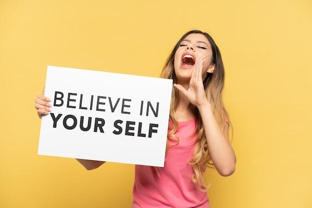 Młoda rosjanka odizolowana na żółtym tle trzymająca tabliczkę z tekstem uwierz w siebie i krzyczącą