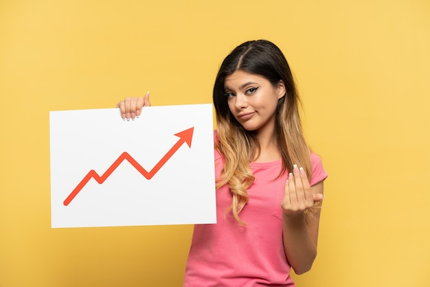 Młoda rosjanka odizolowana na żółtym tle trzymająca znak z rosnącym symbolem strzałki statystyk i wykonująca nadchodzący gest