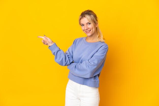 Młoda rosjanka odizolowana na żółtym tle, wskazując palcem w bok