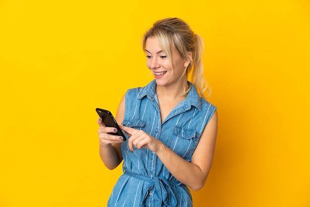 Młoda rosjanka odizolowana na żółtym tle wysyłająca wiadomość lub e-mail za pomocą telefonu komórkowego