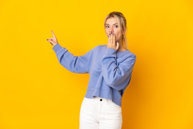 Młoda rosjanka odizolowana na żółtym tle z wyrazem zaskoczenia, wskazując bok