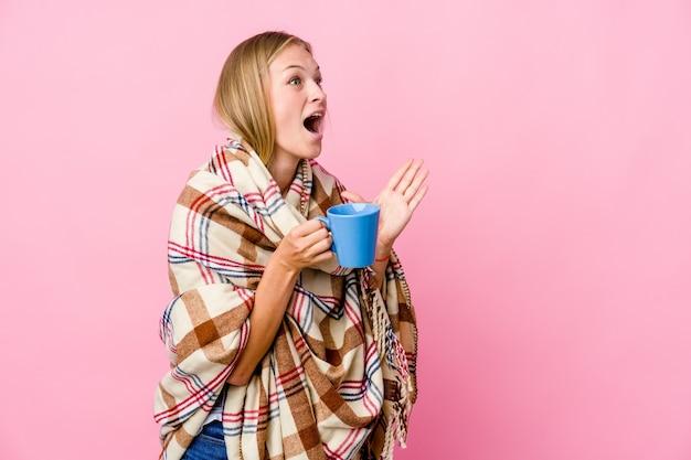 Młoda rosjanka owinięta kocem pijąc kawę krzyczy głośno, ma otwarte oczy i spięte ręce.