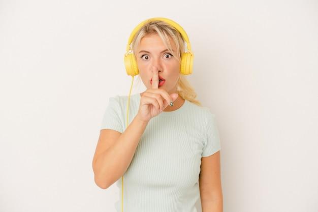 Młoda rosjanka słuchająca muzyki na białym tle dochowująca tajemnicy lub prosząca o ciszę.