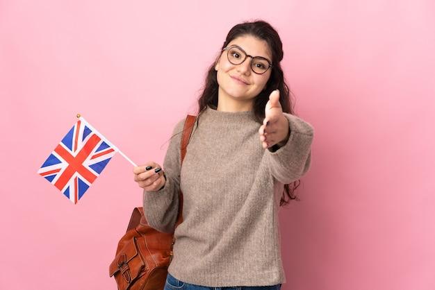 Młoda rosjanka trzyma flagę wielkiej brytanii na białym tle na różowej ścianie, ściskając ręce za zamknięcie dobrej oferty