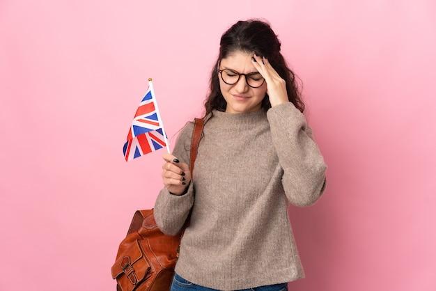 Młoda rosjanka trzyma flagę wielkiej brytanii na białym tle na różowej ścianie z bólem głowy