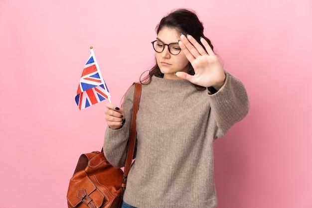 Młoda rosjanka trzyma flagę wielkiej brytanii na białym tle na różowym tle, wykonując gest stop i rozczarowany