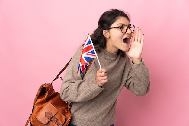 Młoda rosjanka trzyma flagę zjednoczonego królestwa na białym tle na różowym tle, krzycząc z szeroko otwartymi ustami