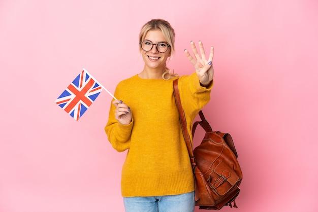 Młoda rosjanka trzyma flagę zjednoczonego królestwa na białym tle na różowym tle szczęśliwa i liczy cztery palcami