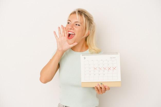 Młoda rosjanka trzyma kalendarz na białym tle krzycząc i trzymając dłoń w pobliżu otwartych ust.