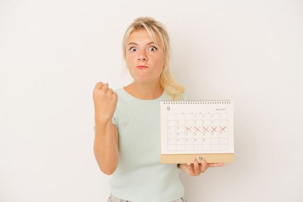 Młoda rosjanka trzyma kalendarz na białym tle, pokazując pięść do kamery, agresywny wyraz twarzy.