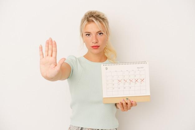 Młoda rosjanka trzyma kalendarz na białym tle stojąc z wyciągniętą ręką pokazując znak stop, uniemożliwiając.