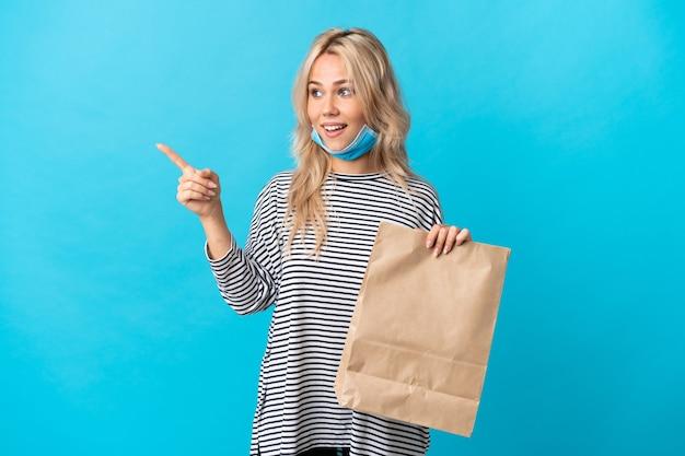 Młoda rosjanka trzyma torbę na zakupy spożywcze na białym tle na niebieski palec wskazujący z boku i prezentuje produkt