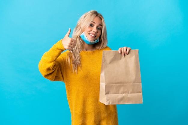 Młoda rosjanka trzyma torbę na zakupy spożywcze na białym tle na niebieskiej ścianie, dając gest kciuki do góry