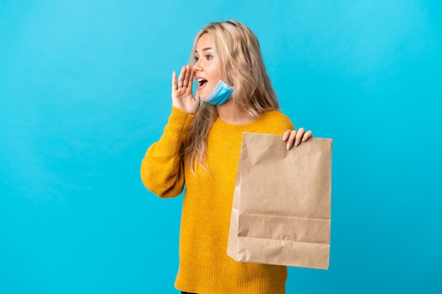 Młoda rosjanka trzyma torbę na zakupy spożywcze na białym tle na niebieskiej ścianie, krzycząc z ustami szeroko otwartymi na bok