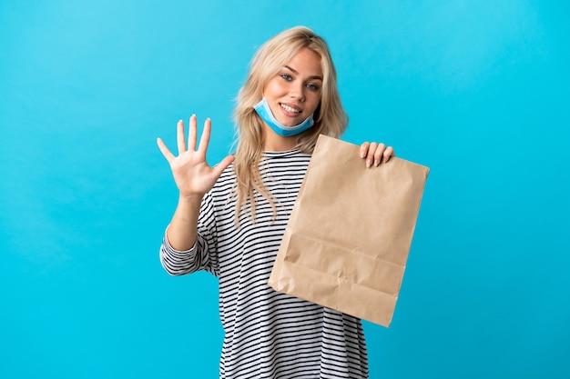 Młoda rosjanka trzyma torbę na zakupy spożywcze na białym tle na niebieskiej ścianie, licząc pięć palcami