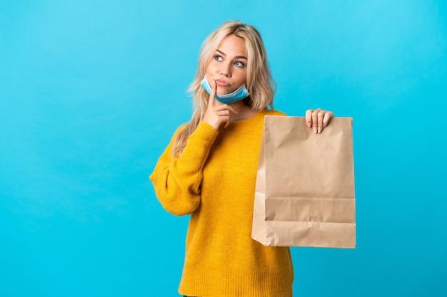 Młoda rosjanka trzyma torbę na zakupy spożywcze na białym tle na niebieskiej ścianie, mając wątpliwości, patrząc w górę