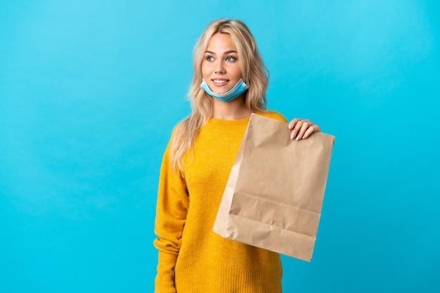 Młoda rosjanka trzyma torbę na zakupy spożywcze na białym tle na niebieskiej ścianie, patrząc z boku i uśmiechając się