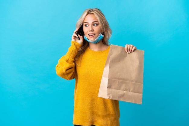 Młoda rosjanka trzyma torbę na zakupy spożywcze na białym tle na niebieskiej ścianie, prowadząc rozmowę z telefonem komórkowym