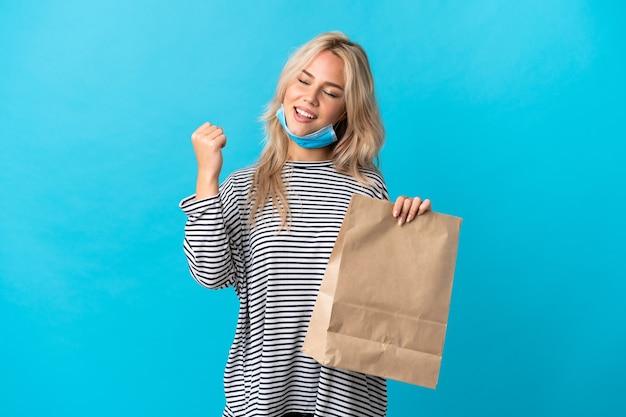 Młoda rosjanka trzyma torbę na zakupy spożywcze na białym tle na niebieskiej ścianie świętuje zwycięstwo