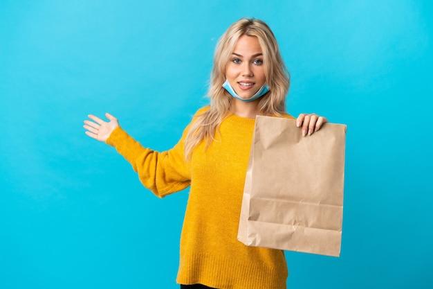 Młoda rosjanka trzyma torbę na zakupy spożywcze na białym tle na niebieskiej ścianie wyciągając ręce na bok za zaproszenie do przyjścia