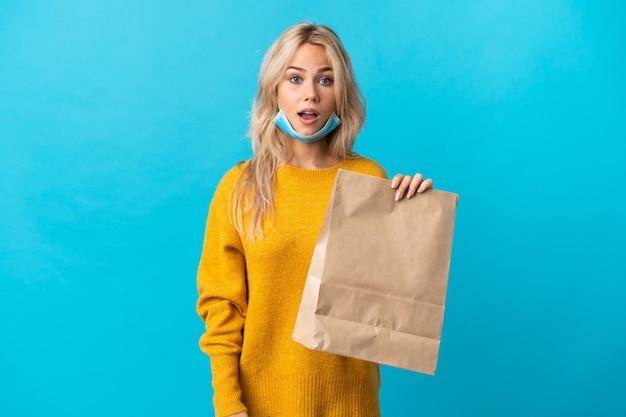 Młoda rosjanka trzyma torbę na zakupy spożywcze na białym tle na niebieskiej ścianie z wyrazem twarzy niespodzianka