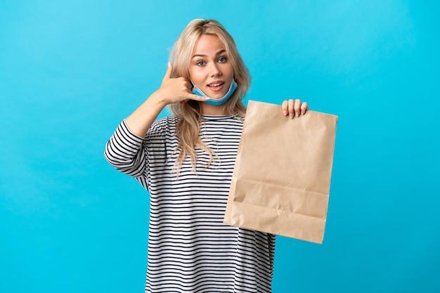 Młoda rosjanka trzyma torbę na zakupy spożywcze na białym tle na niebieskim tle dokonywanie gestu telefonu. oddzwoń do mnie znak
